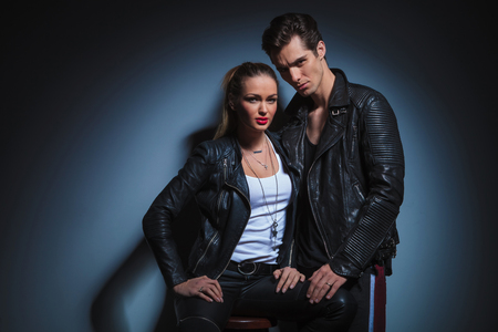 touch down: couple in dark leather posing in studio background. the man is posing looking at the camera and touching her leg while the woman sits on a chair looking at the camera. Stock Photo