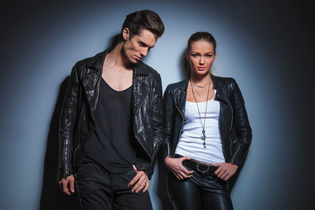 waist down: young rocker looking down with hand in pocket while his girlfriend pose in her leather jacket with hands on waist in studio background