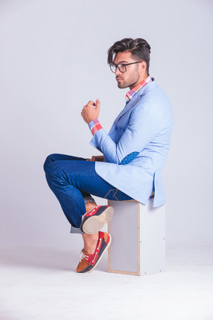 fashionable casual man posing from one side seated on box, with legs crossed while wearing glasses and looking away in studio background Stock Photo