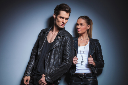starring: sexy biker pose looking away while his woman is starring at him arranging her leather jacket in studio background Stock Photo