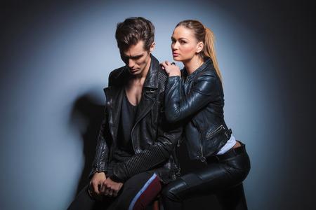 Punk junge Frau stützte sich auf ihren Mann von hinten, während in dunklen Studio-Hintergrund aufwirft. Mann in der Lederjacke schaut nach unten. Standard-Bild
