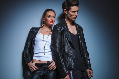 male hair: sexy couple in leather jackets pose in studio background leaning on the wall while looking away