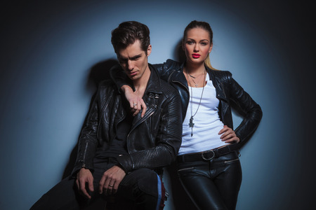 lean on hands: couple in leather jackets posing in studio background. seated man pose for the camera while woman has her hand around his neck