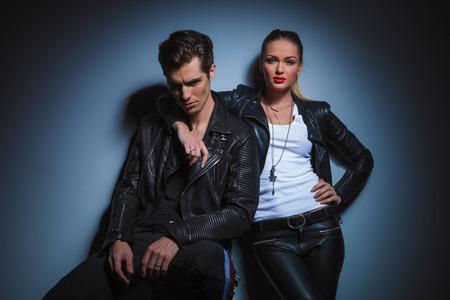 seated man: pareja en las chaquetas de cuero que presenta en fondo del estudio. hombre sentado posar para la cámara mientras que la mujer tiene su mano alrededor de su cuello