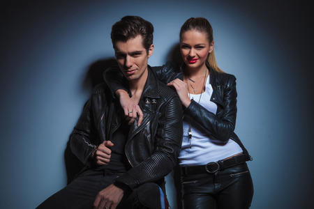 male hair: smiling couple in leather posing in studio background. seated man arranging his jacket while woman rests with hand over his neck