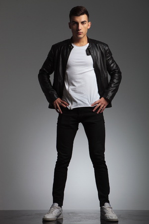 fashion style: attractive man posing spread legs and hands on waist while wearing black leather jacket and looking at the camera in studio background