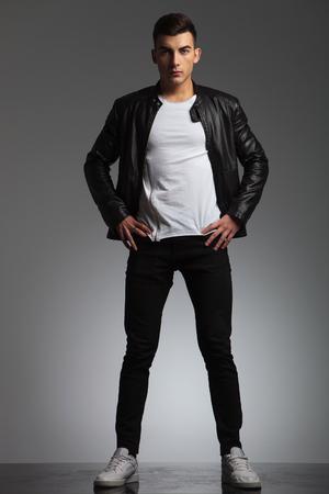 beine spreizen: attraktiver Mann posiert gespreizten Beinen und Händen auf Taille, während schwarze Lederjacke trägt und in die Kamera im Studio Hintergrund suchen