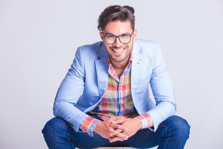Cierre atractivo del hombre presentación retrato sentado con las piernas abiertas y las manos tocando, mientras sonriendo a la cámara en el fondo del estudio