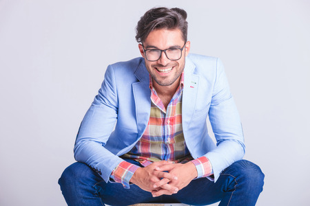 man with glasses: close portrait attractive man posing seated with legs spread open and hands touching, while smiling at the camera in studio background Stock Photo