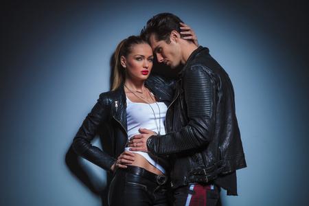 tetona: Hombre atractivo en chaqueta de cuero se inclina contra su novia tetona que plantea que toca su cabeza en el estudio