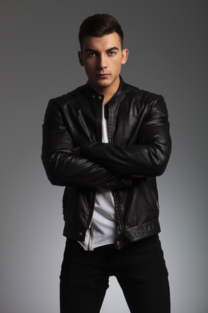 young male: handsome man in black leather jacket pose standing in studio background with hands crossed while looking at the camera