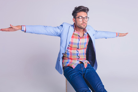 arms wide open: casual man wearing glasses, seated on chair with arms wide open while looking away from the camera
