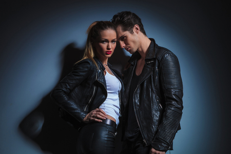 passionate lovers: fashion couple in leather is posing in studio background, the man is looking at the woman while the woman poses with her hand on her waist