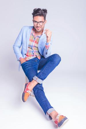 cuerpo hombre: guapo casual posando sentado con las piernas cruzadas y la mano en el bolsillo mientras mira a la cámara en el fondo del estudio