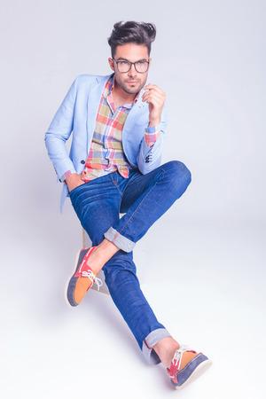 hombre sentado: chico guapo con gafas y pantalones vaqueros que presentan sentado con las piernas cruzadas y la mano en el bolsillo mientras se mira lejos en el fondo del estudio Foto de archivo