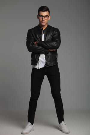 stylish men: attractive man in leather jacket wearing glasses pose in studio background with hands crossed