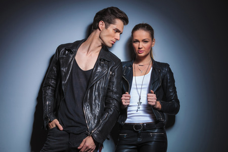 she: sexy fashionable man in black looking at his woman while she is posing for the camera arranging her jacket in studio background