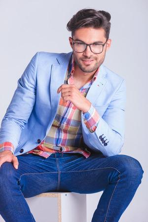 beine spreizen: schließen Porträt sinnlich smart casual Mann mit Beinen sitzt lächelnd spreizt, während die Kamera im Studio Hintergrund suchen