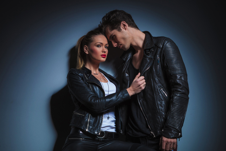 lean on hands: portrait of punk couple in leather posing in dark studio background. the man in starring at the woman while she is pulling his jacket and is lookin at the camera