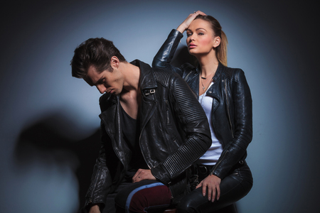 dark side: sexy woman seated behind her man, posing in studio while resting her arm on his back. the man is looking down. Stock Photo