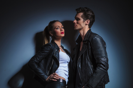 hot couple posing in dark studio background, man looking down on sexy woman in leather jacket Stock Photo