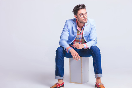 fashionable businessman wearing glasses posing while seated on box looking away from the camera in studio background Foto de archivo
