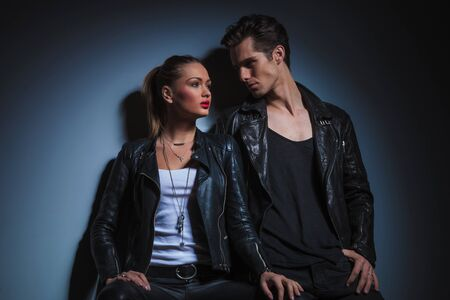 lean on hands: sexy couple in leather pose in dark studio background, man lean on the wall looking at the woman and she pose looking away