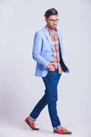 sexy casual guy walking in studio background with hands in pockets while posing looking away from the camera