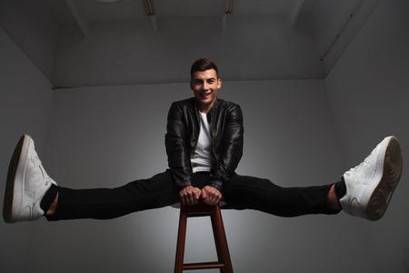 piernas hombre: modelo sonriente en la chaqueta de cuero posando sentado en un taburete con las manos entre las piernas abiertas mientras mira a la cámara en el fondo del estudio