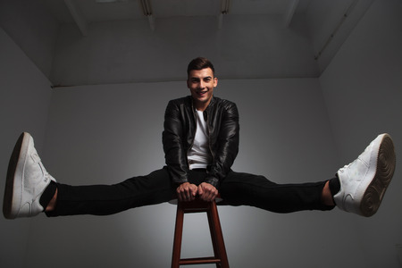 spread legs: smiling model in leather jacket posing seated on stool with hands between spread legs while looking at the camera in studio background