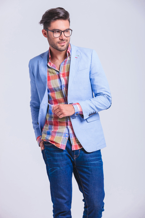 attractive fashionable man wearing glasses walking in studio background with hand in back pocket while looking away from the camera