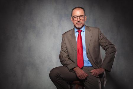 hombres maduros: madurar apuesto hombre de negocios vistiendo traje y gafas haciéndose pasar por sentado mientras mira a la cámara en el fondo del estudio Foto de archivo