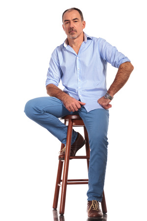 old man sitting: confident mature casual man posing seated on chair while looking at the camera in white isolated studio background