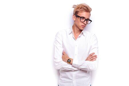 mani incrociate: giovane pantaloni a vita bassa sexy in posa con le mani incrociate mentre indossa gli occhiali e guardare lontano in sfondo bianco studio isolato Archivio Fotografico