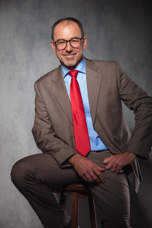 sit on studio: portrait of senior manager wearing glasses posing seated while smiling at the camera in studio background Stock Photo