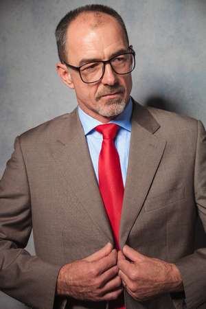 mature businessman: portrait of senior businessman posing in studio background wearing suit and glasses while closing his jacket and looking away