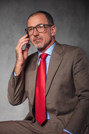 hombres maduros: retrato de gafas de empresario de éxito usando llamadas con su teléfono inteligente mientras se mira lejos en el fondo del estudio