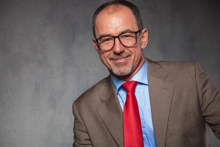 hombres maduros: cerrar el retrato de las gafas, empresario que llevaba barba calvas, exitosos y sonriendo a la cámara en el fondo del estudio