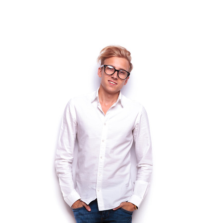 white man: attractive young blonde man posing in white isolated studio background with hands in pockets while looking at the camera wearing glasses