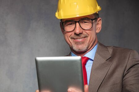 holding close: close portrait of mature engineer wearing helmet and glasses while holding a tablet in studio background Stock Photo