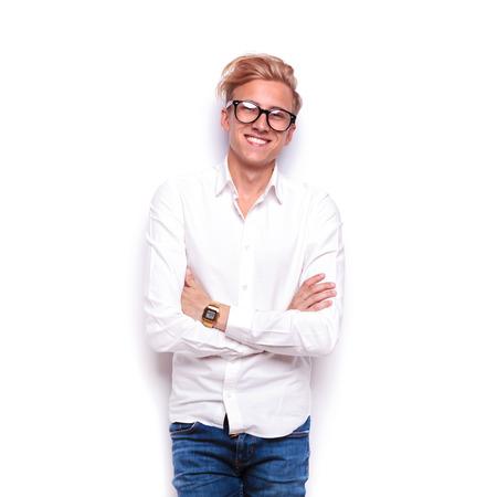 mani incrociate: giovane smart casual in jeans e gli occhiali in posa con le mani incrociate, mentre sorridente in sfondo bianco studio isolato