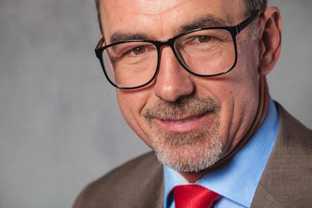 visage homme: près portrait d'affaires d'âge mûr avec des lunettes et sourire tout en posant en studio fond
