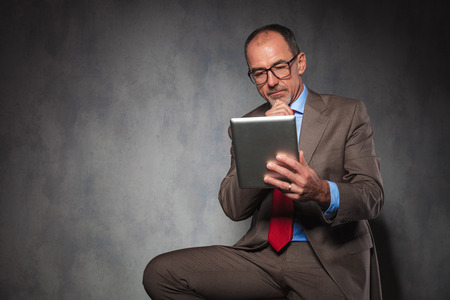 successful man: portrait of succesful mature man in suit wearing glasses, thinking and using his tablet while posing seated in studio background Stock Photo