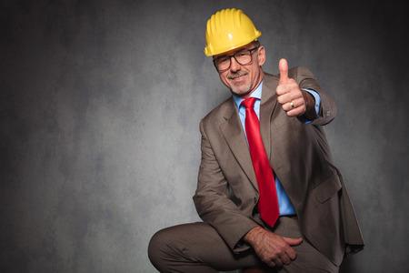 hombres maduros: Retrato del ingeniero elegante con el casco y las gafas mientras se está sentado y mostrando los pulgares para arriba en el fondo del estudio