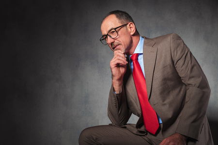 looking away from camera: portrait of mature elegant businessman wearing glasses and looking away from the camera while thinking and posing in studio background