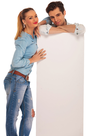 mani incrociate: l'uomo sta dietro bianco cartellone bianco con le mani incrociate mentre la donna riposa il suo braccio sulla sua spalla. Entrambi sono guardando la telecamera in studio isolato sfondo.