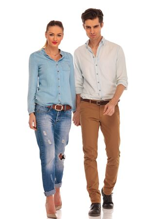 holding hands while walking: attractive casual couple walking in white isolated studio background holding hands while looking at the camera
