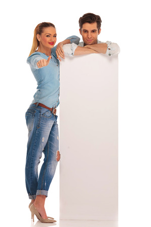 man stands behind white blank billboard with hands crossed while woman shows thumbs up sign in isolated studio background