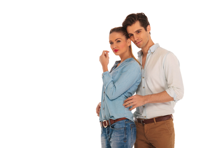 embraced: smiling couple posing embraced in isolated studio background. woman is looking away while man holds her from behind.
