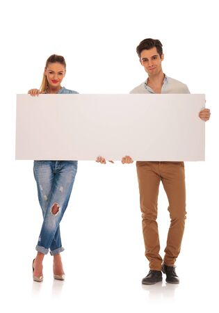 legs crossed: beautiful casual couple posing holding a blank billboard sign looking at the camera. woman has legs crossed in isolated studio background